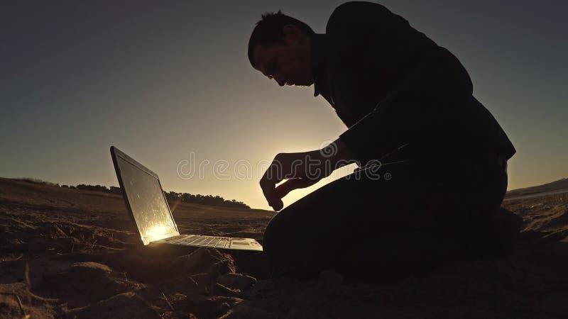 Bemannen Sie den Geschäftsmannlaptopfreiberufler, der hinter dem Sitzen auf freiberuflich tätig seiendem Schattenbild des Strande stockfotografie