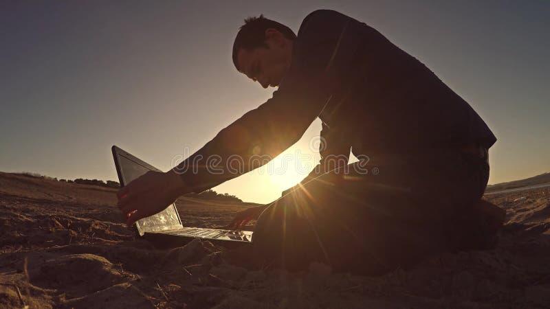 Bemannen Sie den Geschäftsmannlaptopfreiberufler, der hinter dem Sitzen auf freiberuflich tätig seiendem Schattenbild des Strande lizenzfreie stockfotografie