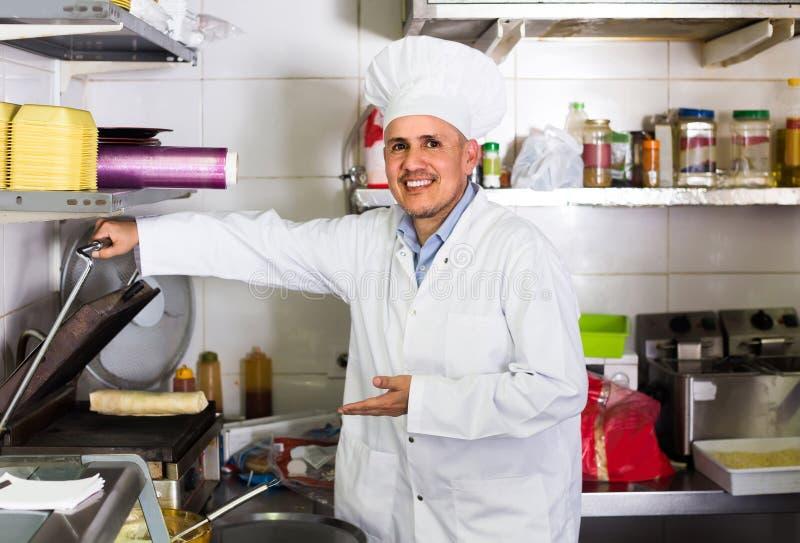 Bemannen Sie den Koch, der Kebabteller auf Küche im Schnellrestaurant macht lizenzfreie stockbilder