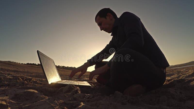 Bemannen Sie den Laptopgeschäftsmannfreiberufler, der hinter dem Sitzen auf freiberuflich tätig seiendem Schattenbild des Strande stockbild