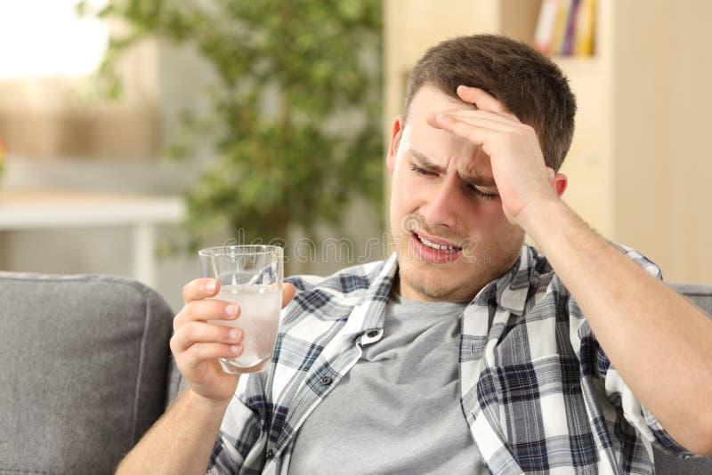 Bemannen Sie den leidenden Hauptschmerz, der ein Schmerzmittel Glas hält lizenzfreies stockbild