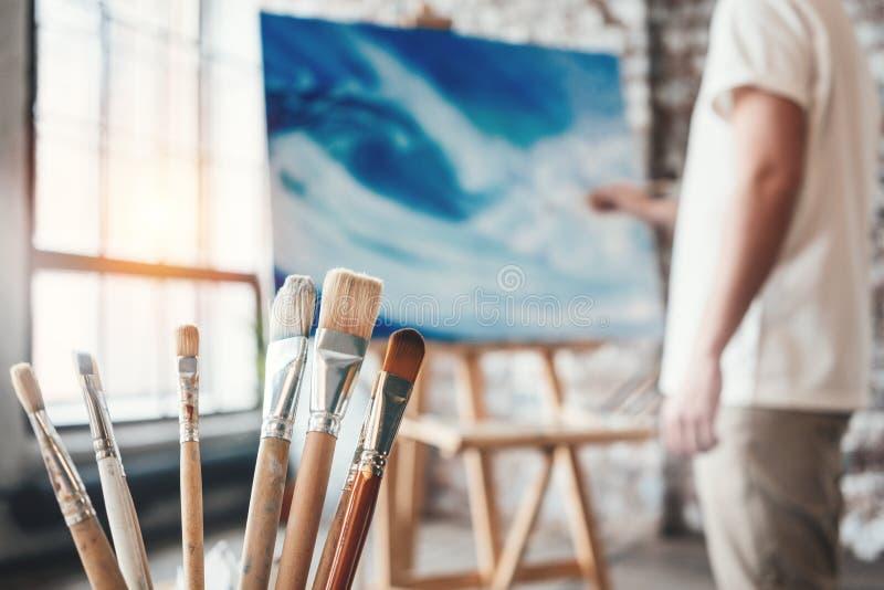 Bemannen Sie den Maler, der in der Werkstatt mit Segeltuch auf Gestell arbeitet Bürsten schließen oben auf Holztisch im Studio Au lizenzfreie stockfotos