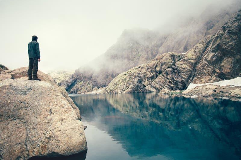 Bemannen Sie den Reisenden, der allein auf Steinklippensee und nebelhaften Bergen auf Hintergrund steht lizenzfreie stockfotos