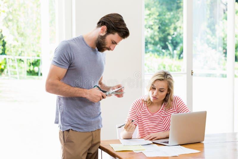 Bemannen Sie den Schnitt einer Kreditkarte während angespannte Frau mit den Rechnungen, die bei Tisch sitzen stockbilder