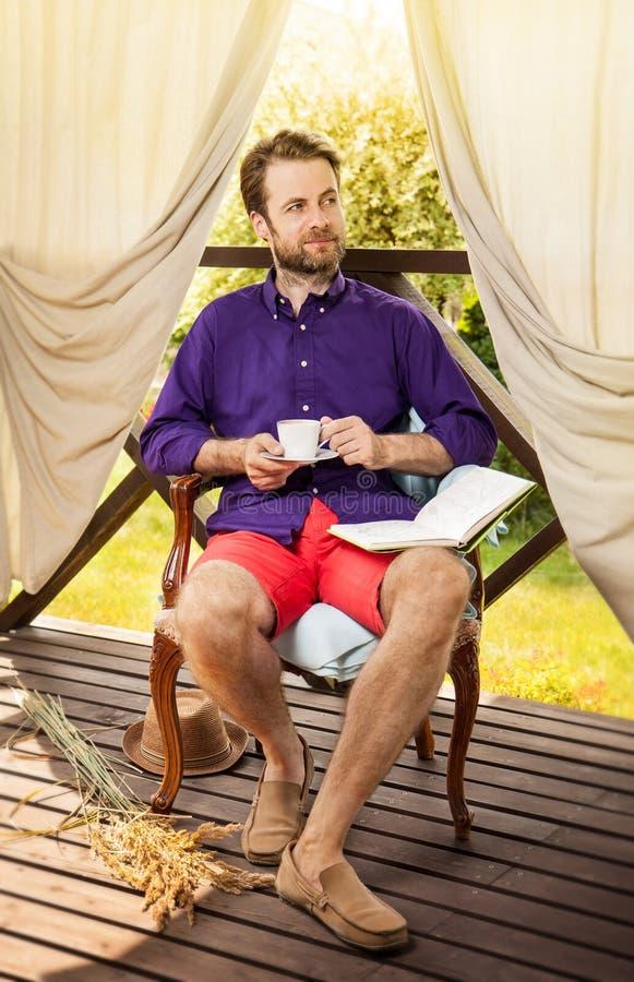 Bemannen Sie den trinkenden Morgenkaffee, der auf Gartenterrasse im Freien ist stockfotografie