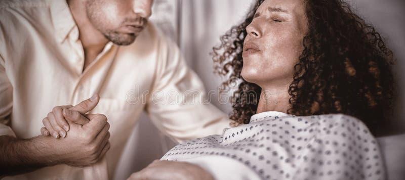 Bemannen Sie den Trost der schwangeren Frau während der Arbeit im Bezirk stockfotografie