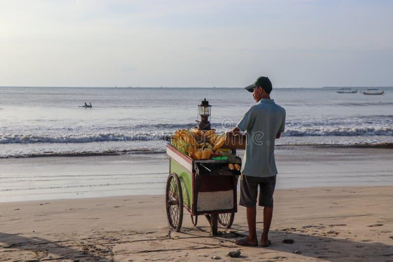 Bemannen Sie den Verkauf von Mais an Jimbaran-Strand in Bali, Indonesien stockbilder