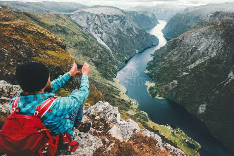 Bemannen Sie den Wanderer, der Foto durch den Smartphone macht, der auf Gebirgsklippe sich entspannt stockfotos