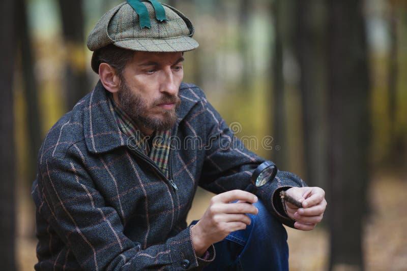 Bemannen Sie Detektiv mit einem Erforschungsbaumfragment des Bartes lizenzfreie stockbilder