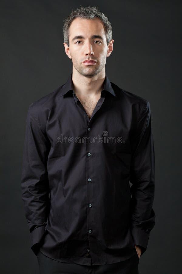 Bemannen Sie die Aufstellung im schwarzen Hemd auf dunklem Hintergrund. stockbild