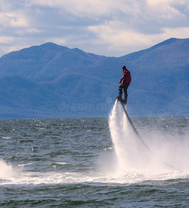 Bemannen Sie die Aufstellung am neuen flyboard an Avacha-Bucht auf Kamchatka lizenzfreie stockfotografie