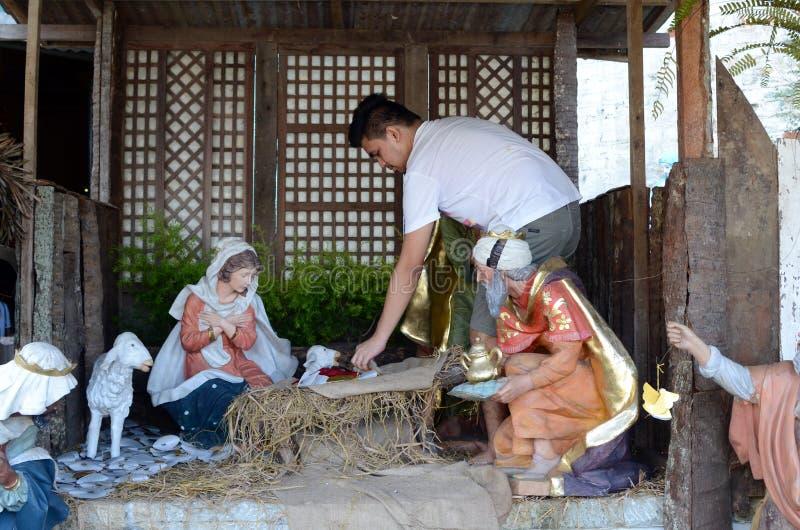Bemannen Sie die beschäftigte vorbereitende Weihnachtskrippe, die mit Statuetten von Mary, von Joseph und von Baby Jesus dargeste lizenzfreie stockbilder
