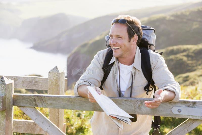 Bemannen Sie die Entspannung auf cliffside Pfad-Holdingkarte stockbilder