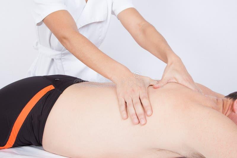 Bemannen Sie die Entspannung auf der Massagetabelle, die Massage durch Frau empfängt stockbilder