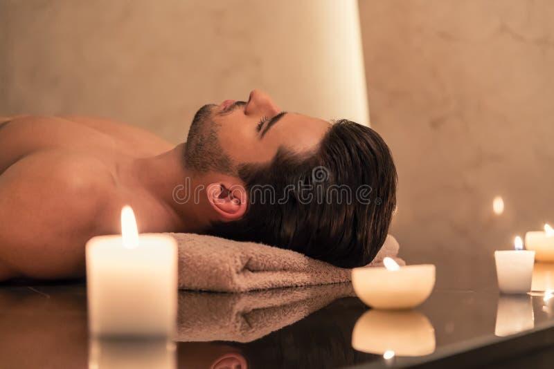 Bemannen Sie die Entspannung auf Massagetabelle in der asiatischen Badekurort- und Wellnessmitte stockbild