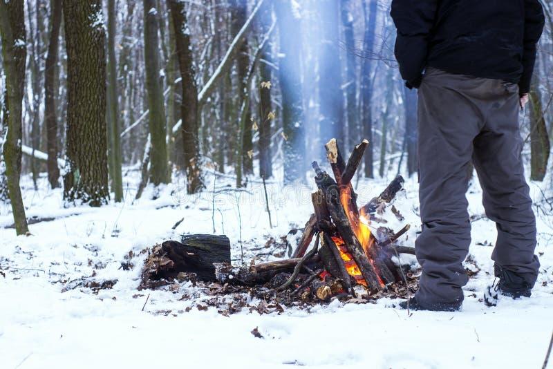 bemannen Sie die Erwärmung seiner Hände um ein Lagerfeuer im Wald lizenzfreie stockfotos