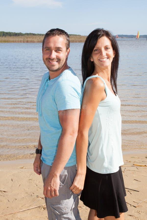 Bemannen Sie die Frauenpaare, die am Strand im Sommer stillstehen lizenzfreie stockfotos