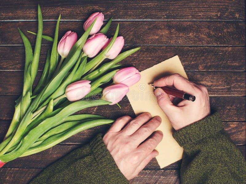 Bemannen Sie die Hände, die auf Blätter des leeren Papiers auf altem Holztisch bunc schreiben stockfoto