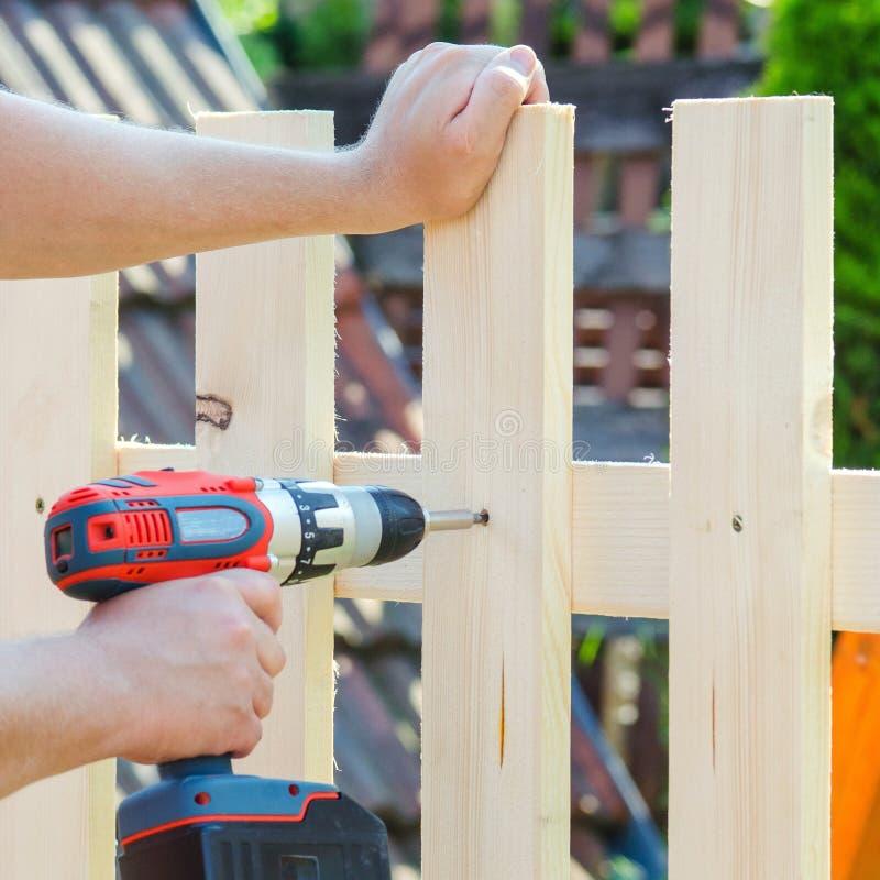 Bemannen Sie die Hände, die Bretterzaun mit einem Bohrgerät und einer Schraube errichten DIY Konzept Schließen Sie oben von seine stockfotos