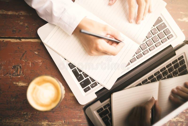 Bemannen Sie die Hände, die in das Tagebuch, in die Kaffeetasse und in den Laptop auf hölzernes schreiben stockbild