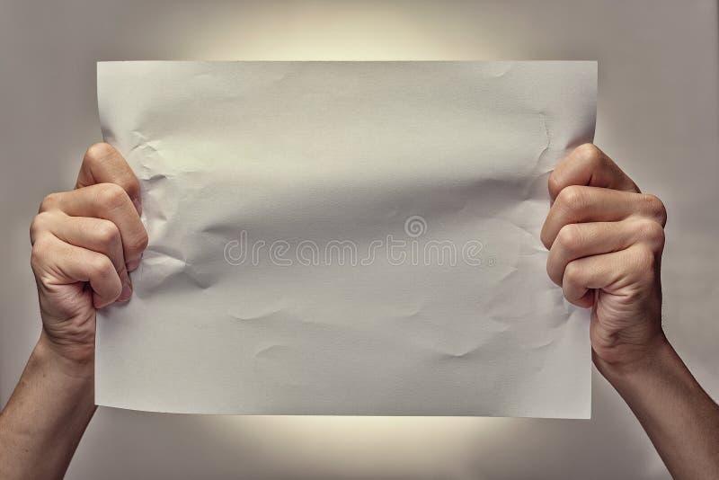 Bemannen Sie die Hände, die ein zerknittertes leeres Blatt Papier halten stockfotos