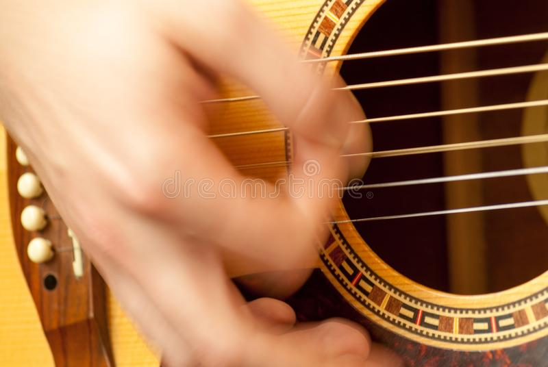 Bemannen Sie die Hand, die Akustikgitarreschnurerholungskonzept spielt lizenzfreie stockfotos