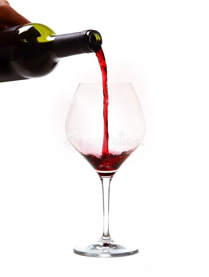 Bemannen Sie die Hand, die das Flaschenfüllen Glas mit Rotwein hält stockfotos