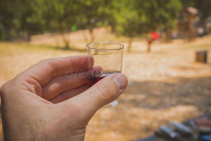 Bemannen Sie die Hand, die ein Schnapsglas mit Rotwein bei einer Sozialsitzung hält stockbilder