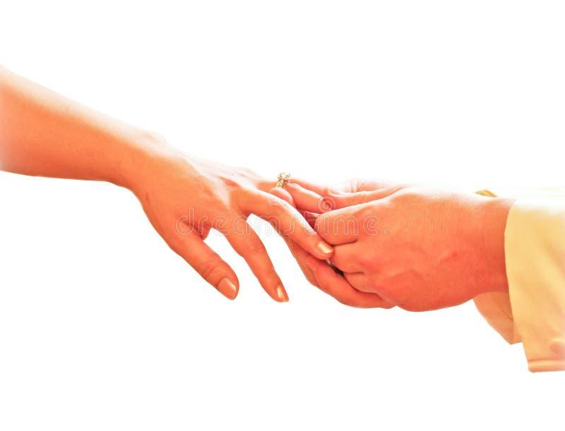 Bemannen Sie die Hand, die einen Hochzeitsring auf Brautfinger setzt stockfotografie
