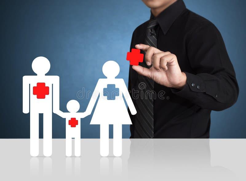 Bemannen Sie die Hand, die Versicherungssymbol mit Papierfamilie hält stockbilder