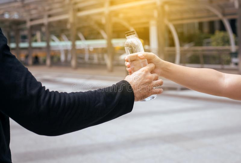 Bemannen Sie die Hand, die Flasche Trinkwasser nach laufender Übung an der Straße gibt stockbild