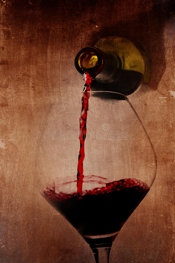 Bemannen Sie die Hand, welche die Flasche hält, die das Rotweinfüllen Glas auf Artyhintergrund gießt stockfotos