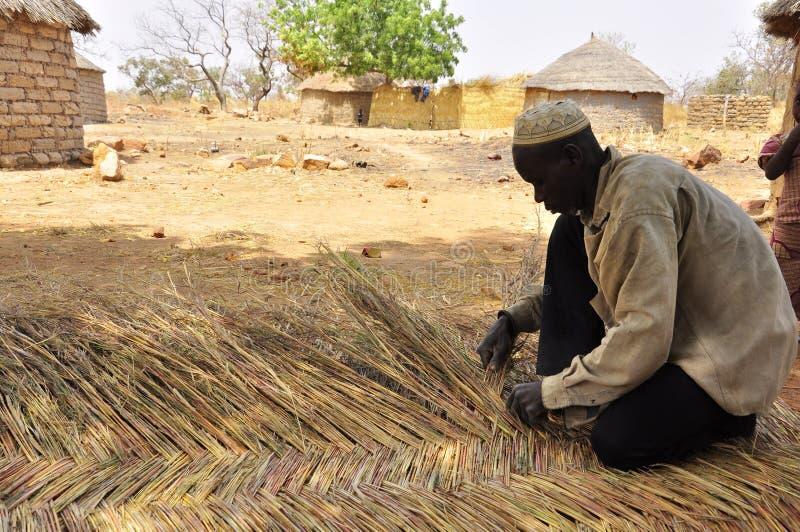 Bemannen Sie die Herstellung der Strohwand für afrikanische Häuser, Dach lizenzfreie stockfotos
