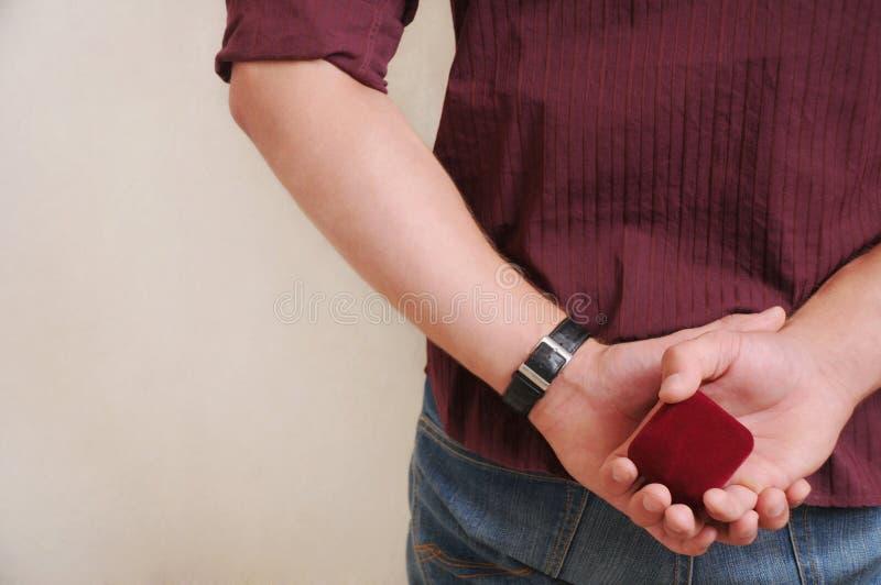 Bemannen Sie die Herstellung des Antrages mit Ehering und Geschenkbox, die conc Heirat stockfotografie