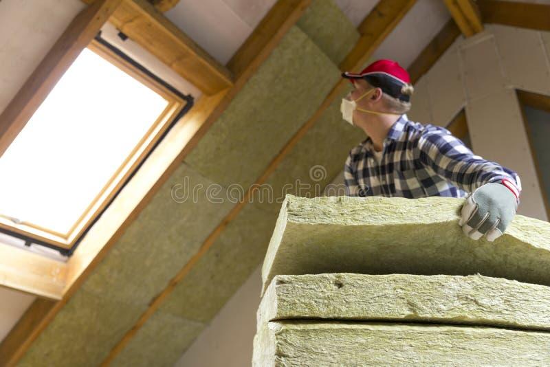 Bemannen Sie die Installierung der thermischen Dachdämmschicht - unter Verwendung des Minerals flehen Sie an lizenzfreie stockbilder