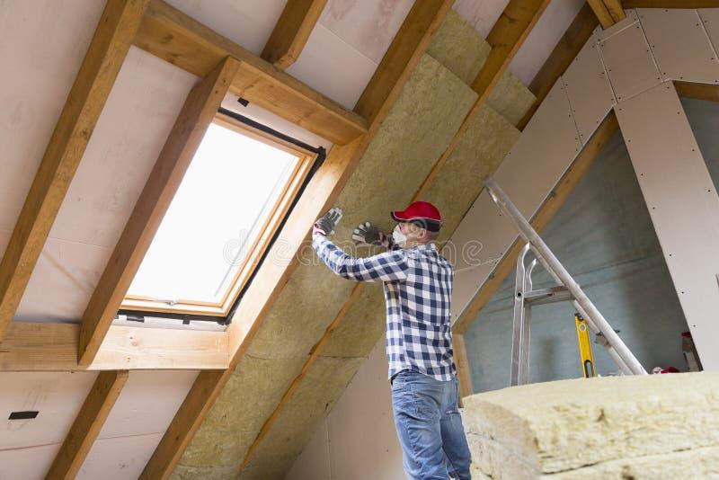Bemannen Sie die Installierung der thermischen Dachdämmschicht - unter Verwendung des Minerals flehen Sie an stockfoto