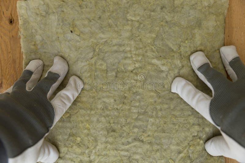 Bemannen Sie die Installierung der thermischen Dachdämmschicht - unter Verwendung des Minerals flehen Sie an lizenzfreies stockbild
