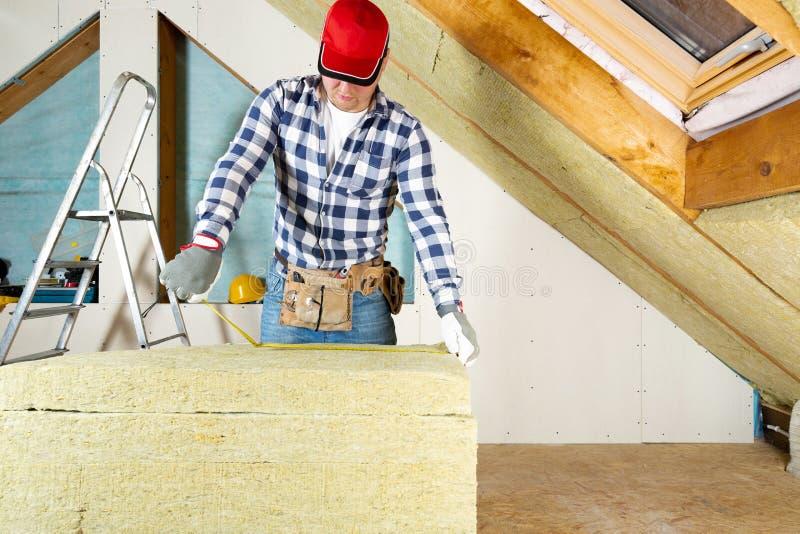 Bemannen Sie die Installierung der thermischen Dachdämmschicht - unter Verwendung des Minerals flehen Sie an stockbild