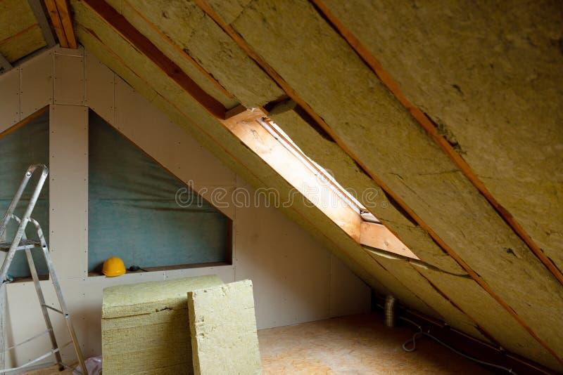 Bemannen Sie die Installierung der thermischen Dachdämmschicht - unter Verwendung des Minerals flehen Sie an stockfotografie