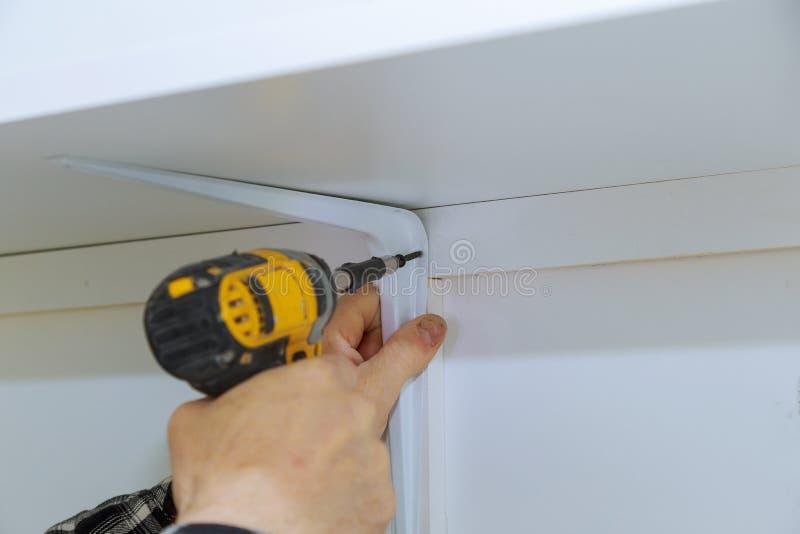 Bemannen Sie die Installierung von hölzernen Regalen auf die Klammerwand, die ein Regal installiert lizenzfreies stockfoto