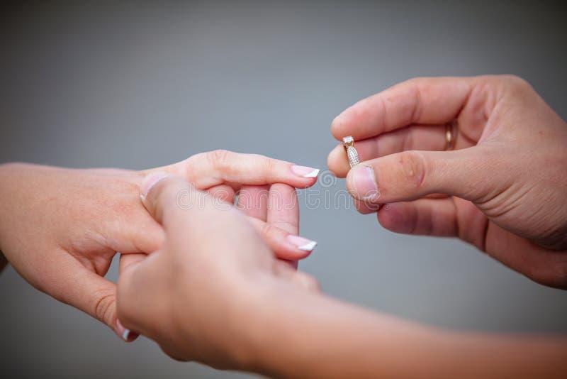 Bemannen Sie die Platzierung eines DiamantVerlobungsrings auf Finger seines Verlobten lizenzfreie stockfotografie