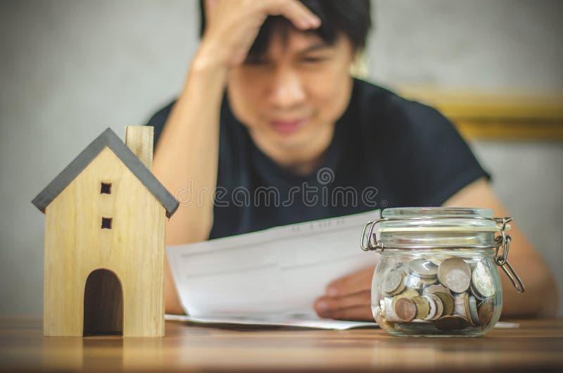 Bemannen Sie die Prüfung von Rechnungen und Haben von Finanzproblemen mit Hauptschuld, Geldkonzept , kaufen Immobilien, eine Wohn lizenzfreies stockfoto