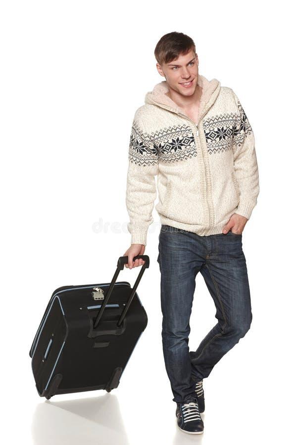 Bemannen Sie die tragende warme Jacke, die mit Reisekoffer geht lizenzfreie stockfotografie