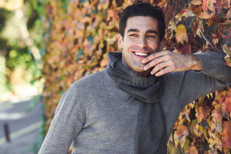 Bemannen Sie die tragende Winterkleidung, die im Herbstlaubhintergrund lächelt stockfotos