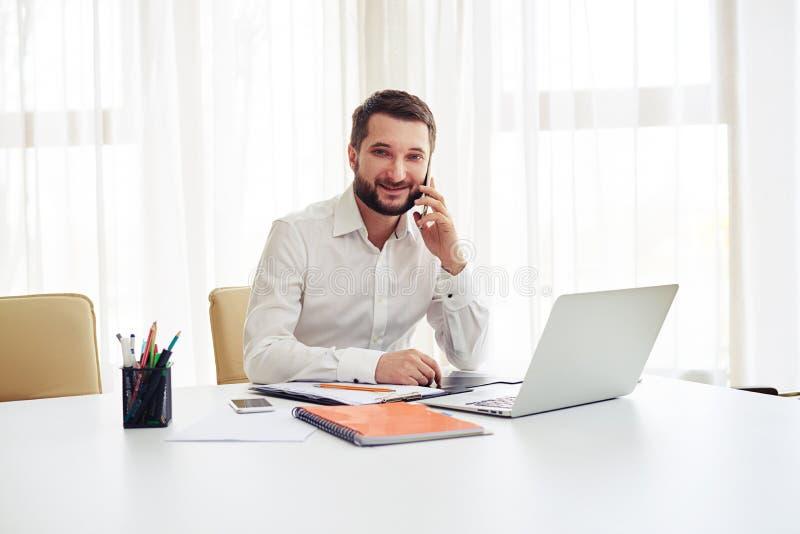 Bemannen Sie die Unterhaltung auf dem Smartphone im modernen weißen Büro lizenzfreies stockbild