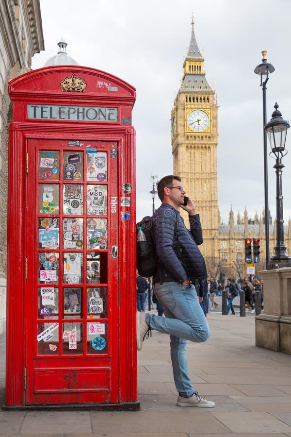 Bemannen Sie die Unterhaltung auf Handy, roter Telefonzelle und Big Ben London, England lizenzfreie stockfotografie