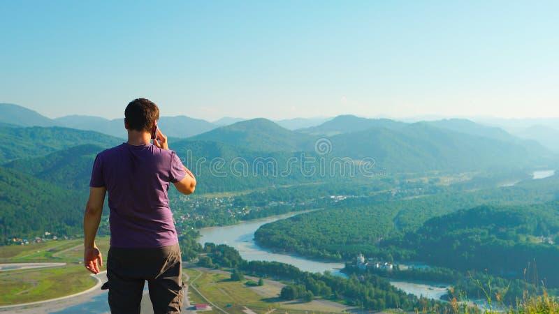 Bemannen Sie die Unterhaltung an einem Handy auf Berglandschaftshintergrund lizenzfreie stockfotografie