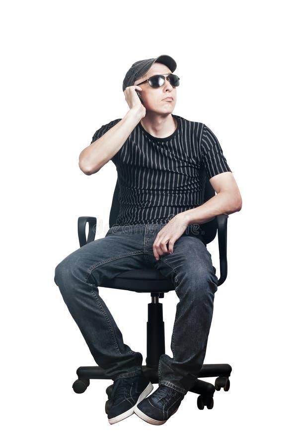 Bemannen Sie die Unterhaltung am Handy beim Sitzen in einem Bürostuhl lizenzfreies stockbild
