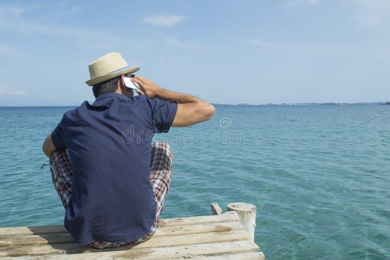 Bemannen Sie die Unterhaltung an seinem Handy am Pier stockbilder