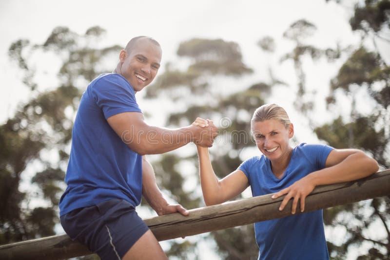 Bemannen Sie die Unterstützung der Frau, um Hürden zu klettern während des Hindernistrainings lizenzfreies stockbild